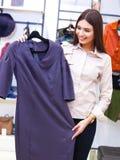 Compras hermosas de la mujer y mirada de un poco de ropa Imagen de archivo