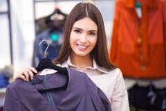 Compras hermosas de la mujer y mirada de un poco de ropa Imagenes de archivo