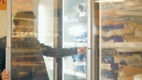 Compras hermosas del hombre en un supermercado, tomando la comida congelada del congelador almacen de video