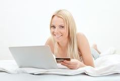 Compras hermosas jovenes de la mujer usando la computadora portátil Fotografía de archivo libre de regalías