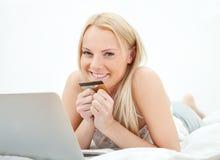 Compras hermosas jovenes de la mujer usando la computadora portátil Imagen de archivo