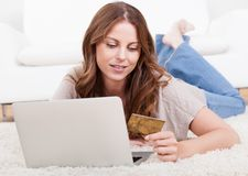 Compras hermosas jovenes de la mujer usando la computadora portátil Fotografía de archivo