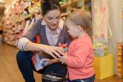 Compras jovenes de la hija de la madre en la tienda de juguete Fotos de archivo libres de regalías