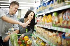 Compras jovenes de los pares en el supermercado Fotos de archivo libres de regalías