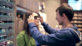 Compras jovenes de los pares en la tienda, gafas de sol de la compra metrajes