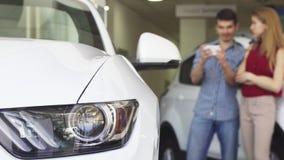 Compras jovenes de los pares para un nuevo automóvil en el saon del delership almacen de metraje de vídeo