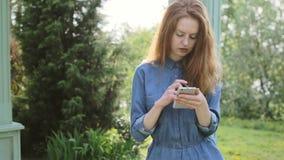 Compras jovenes del teléfono móvil del uso de la mujer del redhair en línea y paga con actividades bancarias de Internet almacen de video