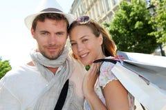 Compras jovenes sonrientes de los pares en ciudad Foto de archivo libre de regalías