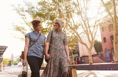 Compras lesbianas jovenes sonrientes de los pares en la ciudad Imagen de archivo