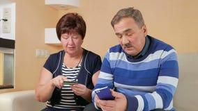 Compras mayores de los pares en tienda de Internet por la tarjeta y el teléfono de crédito El hombre y la mujer que sientan en ca metrajes