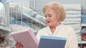 Compras mayores encantadoras de la señora para el lecho en la tienda de muebles almacen de video