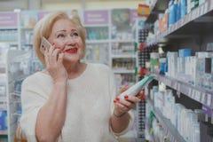 Compras mayores preciosas de la mujer en la droguer?a fotografía de archivo
