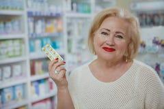 Compras mayores preciosas de la mujer en la droguer?a foto de archivo