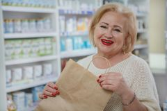 Compras mayores preciosas de la mujer en la droguer?a fotografía de archivo libre de regalías