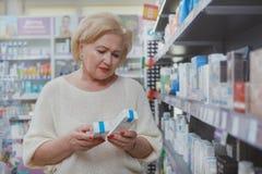 Compras mayores preciosas de la mujer en la droguer?a foto de archivo libre de regalías
