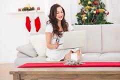 Compras morenas bonitas en línea con el ordenador portátil en los chistmas Fotos de archivo