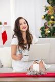 Compras morenas sonrientes en línea con el ordenador portátil en la Navidad Imágenes de archivo libres de regalías