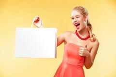 Compras A mulher de sorriso nova que mostra o saco da venda faz seu polegar acima no feriado preto de sexta-feira Menina no fundo fotografia de stock