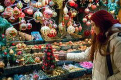 Compras por días de fiesta de la Navidad, mujer joven en la ventana de exhibición del mercado que elige decoraciones del árbol fotos de archivo