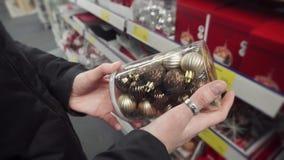 Compras por días de fiesta de la Navidad, mujer que elige las bolas de oro para el árbol de Navidad 4K UltraHD metrajes