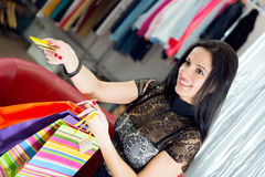 Compras sonrientes de la chica joven con la tarjeta de crédito Fotografía de archivo