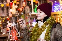 Compras sonrientes de la chica joven en la feria festiva Imagen de archivo