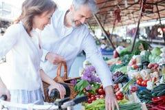 Compras sonrientes felices del marido y de la esposa para los ultramarinos y la comida fresca en un mercado imagen de archivo