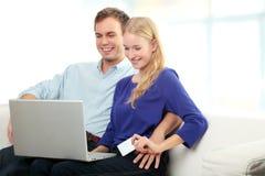 Compras sonrientes jovenes de los pares en Internet Foto de archivo libre de regalías