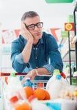 Compras tristes del hombre en el supermercado Fotografía de archivo