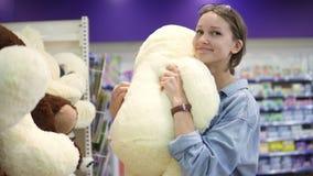 Compratore di donna sorridente positivo felice felice che sceglie i giocattoli dagli shelfs del supermercato Prende un grande un  stock footage