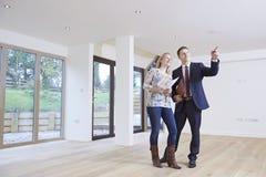 Compratore di Showing Prospective Female dell'agente immobiliare intorno alla proprietà Fotografia Stock