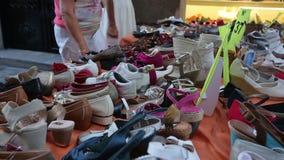 Compratori interessati che scelgono le scarpe delle donne sulla stalla di acquisto della via, mercato locale stock footage
