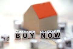 Compre agora o texto soletrado com os grânulos telhados da letra e uma casa borrada do modelo pequeno fotos de stock royalty free