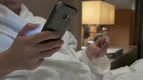 Compre en l?nea con su tarjeta del smartphone y de cr?dito Las manos femeninas utilizan la tarjeta y el tel?fono en la tarde en e almacen de video
