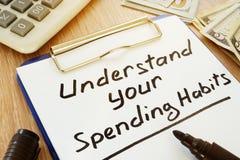 Compreenda seus hábitos da despesa escritos na prancheta foto de stock