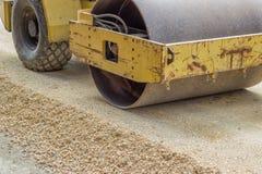 Compresor vibratorio amarillo del tambor de acero durante la construcción de carreteras Fotos de archivo