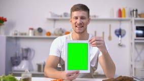 Compressa bella della tenuta dell'uomo con lo schermo verde, cucinante applicazione di corsi stock footage