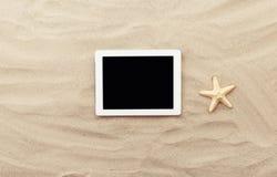 Compressa bianca con lo schermo in bianco sulla sabbia Fotografie Stock