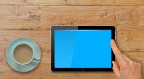Compressa del computer con la mano che indica o che Swiping sulla Tabella dalla tazza di tè o del caffè Immagine Stock