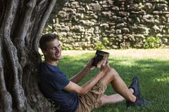 Compressa della lettura dell'uomo e godere del resto in un parco sotto l'albero immagine stock