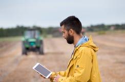 Compressa della tenuta dell'agricoltore con il trattore dietro Fotografia Stock Libera da Diritti