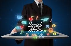 Compressa della tenuta dell'uomo d'affari con i grafici sociali di media Immagine Stock