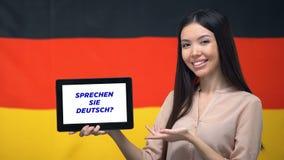 Compressa della tenuta della donna con farvi per parlare frase tedesca, app per l'apprendimento della lingua stock footage