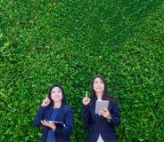 Compressa della tenuta della donna di affari di due asiatici e dito del punto fino a ai fotografia stock libera da diritti