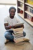 Compressa di With Books And Digital dello studente che si siede dentro Immagini Stock