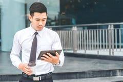 Compressa di With Coffee Using Digital dell'uomo d'affari alla città fuori fuori immagine stock