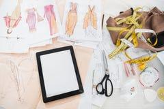 Compressa di Digital con i modelli e nastri di misurazione con le forbici fotografie stock