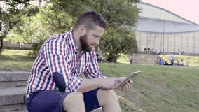 Compressa di lettura rapida del giovane, sedentesi sulle scale colpo del cursore video d archivio