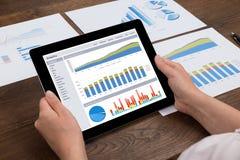 Compressa di Person Analyzing Financial Statistics On Digital Fotografia Stock Libera da Diritti