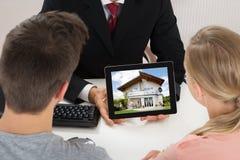 Compressa di Showing House On Digital dell'agente da coppia immagine stock